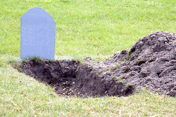 Shallow open grave with blank tombstone